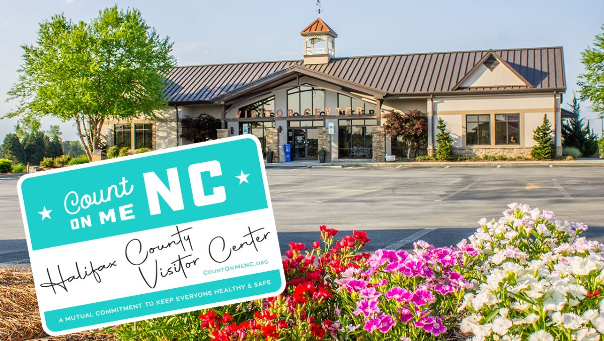 exterior of halifax county visitor center with colorful flowers and sticker of a name tag for count on me nc